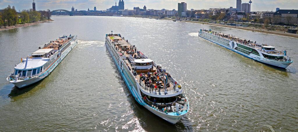 drei flusskreuzfahrtschiffe auf dem wasser